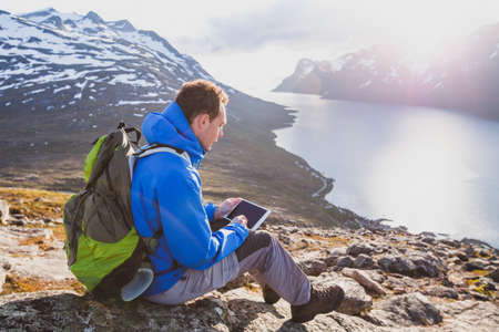man tourist backpacker using internet application on tablet computer outside in mountains