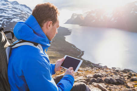 traveler backpacker using digital tablet computer outside in mountains, mobile travel application online