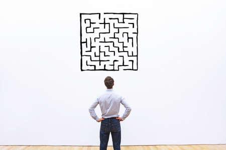 Zakenman kijken naar labyrint tekening, ingewikkeld moeilijk oplossing concept Stockfoto