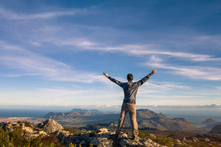 man standing with raised hands on top of Table mountain in Cape Town, South Africa 版權商用圖片 - 82500919
