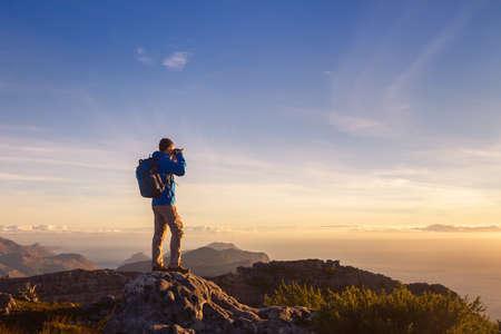 Natuurfotograafreiziger die foto van prachtig landschap van bovenop de berg neemt