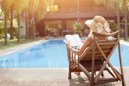 relaxation concept, woman reading book near swimming pool of hotel Фото со стока