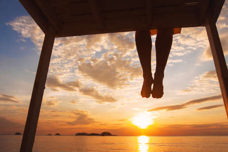 mindfulness concept, woman enjoying summer evening on the beach at sunset, silhouette of feet of happy girl sitting alone on the pier Stockfoto