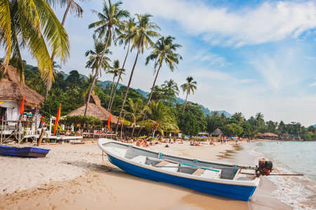 beautiful tropical beach in Thailand, wooden boat and palm trees on Koh Chang