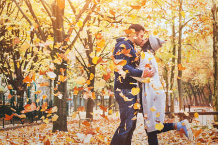 autumn love, couple kissing in fall park, happy man and woman outside Фото со стока