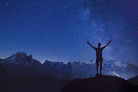 person looking at night starry sky , silhouette of man standing with raised hands dreaming about stars