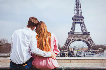 romantic holidays in France, couple sitting together near Eiffel tower in Paris, honeymoon travel Фото со стока