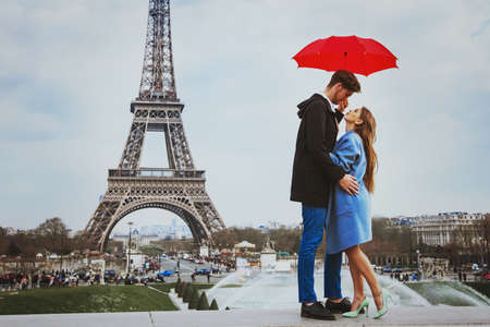 romantic affectionate couple kissing under  umbrella near Eiffel Tower, honeymoon in Paris