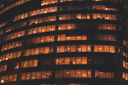 yellow light in windows of office building by night, business tower exterior