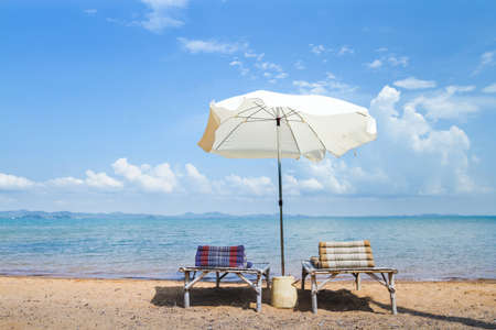 beach holidays, two deck chairs and umbrella near the sea, summer relaxation concept Фото со стока