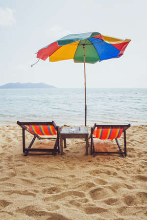 beach in Thailand, two deck chairs and colorful umbrella near the sea