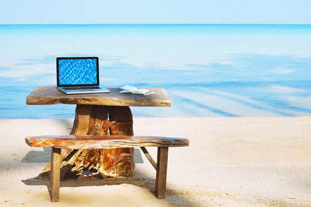 office of freelancer on the beach, laptop computer with empty screen and nobody, freelance concept Stock Photo