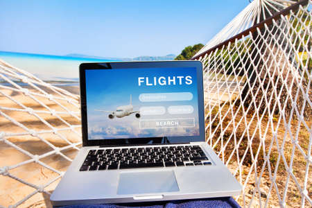 search flight tickets on internet, buy online website on the screen of laptop computer Фото со стока