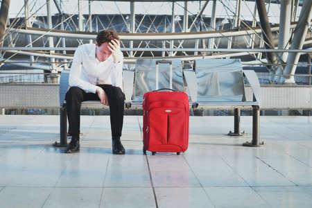 Retraso del vuelo o problema en el aeropuerto, pasajero desesperado y cansado esperando en la terminal con maleta Foto de archivo