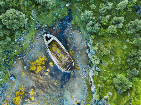 beautiful aerial shot of abandoned wooden boat on the beach Фото со стока
