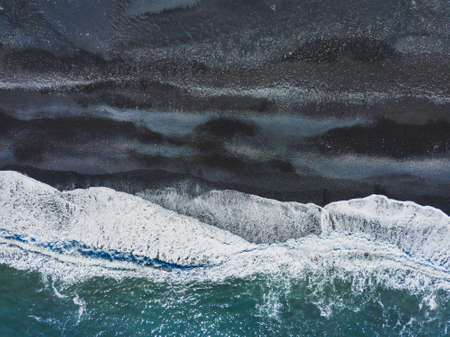 aerial shot of waves on black sand beach in Iceland, top view landscape from drone