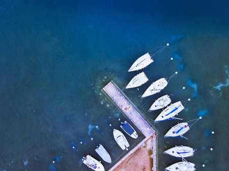 aerial view of boats parked near pier on the lake, blue water landscape from drone Stock fotó