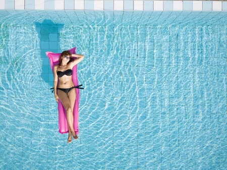 woman in bikini relaxing on inflatable mattress in the swimming pool of hotel, beach vacation, holidays background with copy space