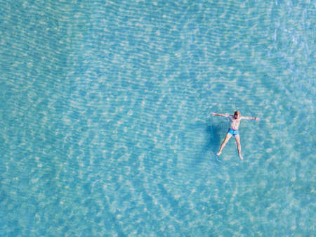 man swimming in turquoise water from above, top view of tourist relaxing in the sea on paradise beach with copy space