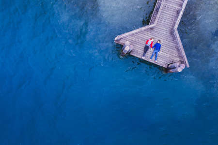 romantic couple lying on the wooden pier on lake with blue water, love and dating concept, background with copyspace Фото со стока