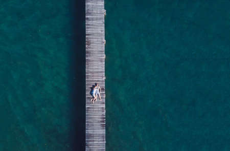 travel background with copy space, drone aerial view of honeymoon romantic couple lying down on wooden pier, beach holidays