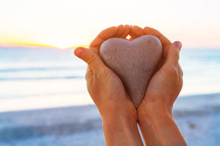 love or giving concept, hands holding heart at sunset beach
