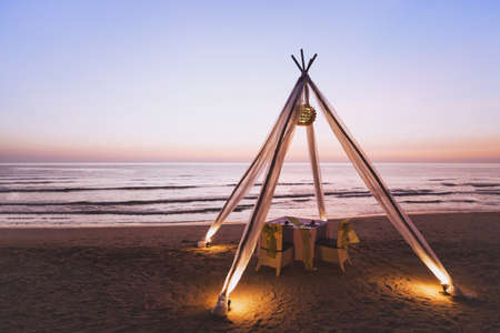 honeymoon dinner for wedding couple on the beach in luxurious romantic hotel, beautiful table for two at sunset