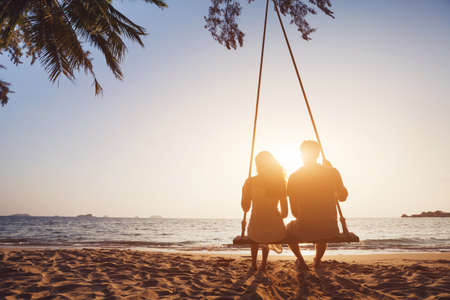 romantic couple in love sitting together on rope swing at sunset beach, silhouettes of young man and woman on holidays or honeymoon Фото со стока