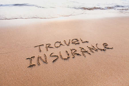 travel insurance concept, text words written on the sand