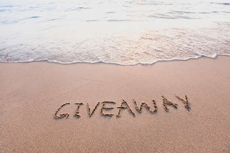 giveaway concept, word message written on the sand 写真素材