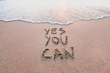 yes you can, motivational inspirational message concept written on the sand of beach Stock Photo