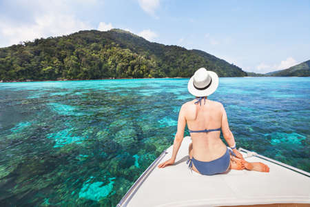 beautiful woman tourist sitting on luxurious boat on paradise tropical beach, holidays travel, exotic vacation