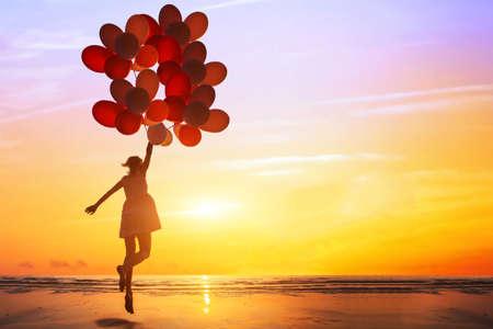 concept de bonheur ou de rêve, silhouette de femme heureuse sautant avec des ballons multicolores au coucher du soleil sur la plage