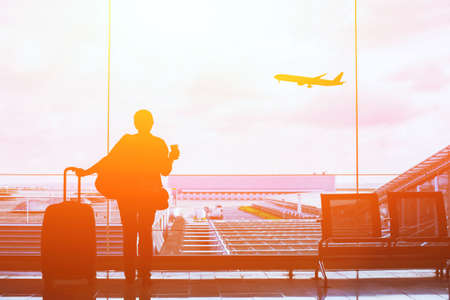 people in airport waiting for departure, silhouette of woman passenger traveling with luggage Stock Photo
