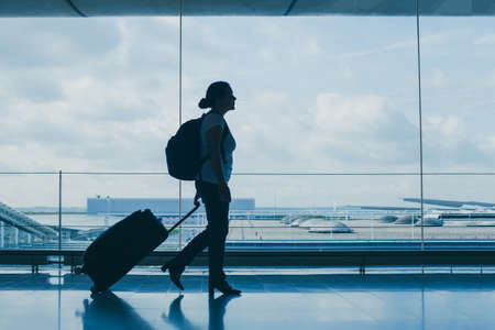 departures in airport, silhouette of woman walking with suitcase, travel background with copy space