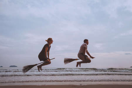 holiday travel with friends, creative transportation  mode, flight on broomstick, people having fun on the beach
