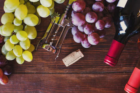 wine bottles, grape and corkscrew top view on wood background 스톡 콘텐츠