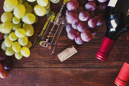 wine bottles, grape and corkscrew top view on wood background 版權商用圖片