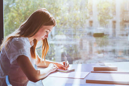 education, student girl in university during exam, young woman studying, people writing test Banco de Imagens