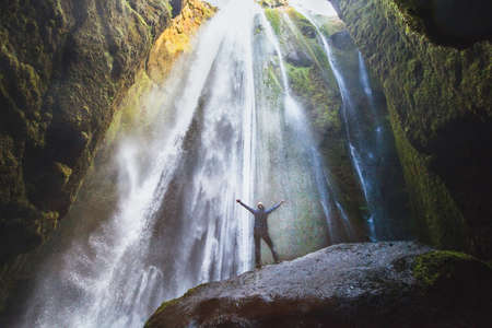 travel to Iceland, person with raised hands standing in waterfall Gljufrabui, inspired happy traveler enjoying nature, adventure concept