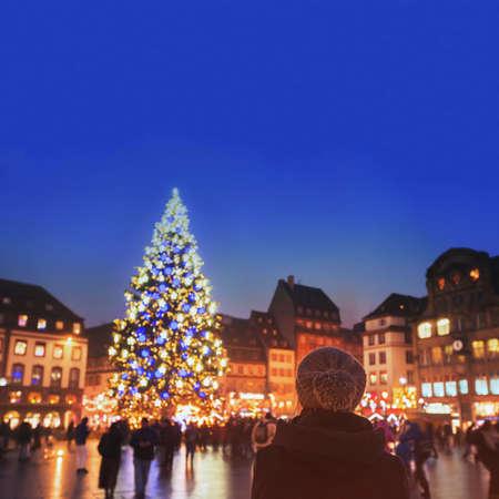 Weihnachtsmarkt in Europa, geschmückter Weihnachtsbaum auf der Straße der Stadt, Frau mit warmem Hut, die gemütliche Atmosphäre genießt