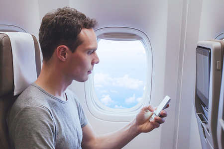 passenger using mobile phone smartphone in the airplane, wifi connection in plane during flight