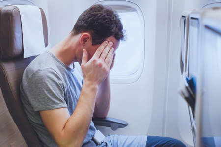 headache in the airplane, man passenger afraid and feeling bad during the flight in plane Stockfoto