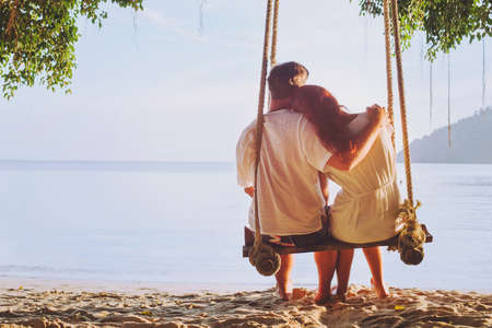 romantic holidays for two, affectionate couple sitting together on the beach on swing, silhouette of man hugging woman Stock Photo