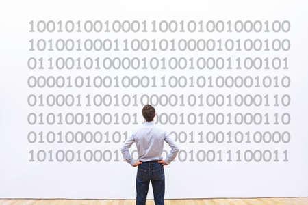 programmatore uomo che guarda il codice binario, il concetto di codifica, la crittografia dei dati