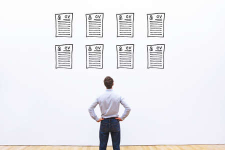 human resource manager looking at many different cv resume and choosing perfect person to hire Stock Photo - 111082543