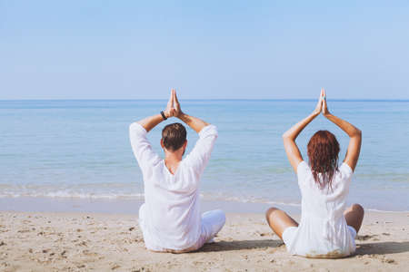 yoga on the beach, two people in white clothes practicing meditation, healthy lifestyle background