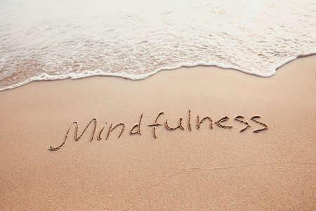 Achtsamkeitskonzept, achtsames Leben, Text auf dem Sand des Strandes geschrieben