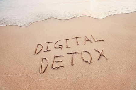 digital detox concept, words written on the sand of beach 스톡 콘텐츠