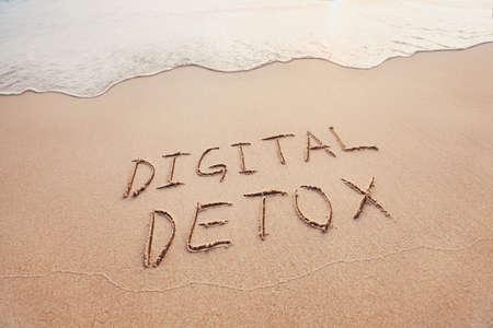 digitales Detox-Konzept, Worte auf dem Sand des Strandes geschrieben Standard-Bild